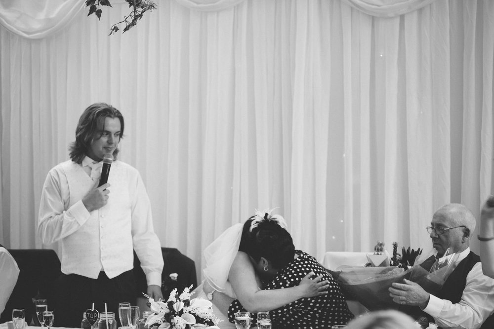 Black and white photo of bride and mam hugging during groom's speech