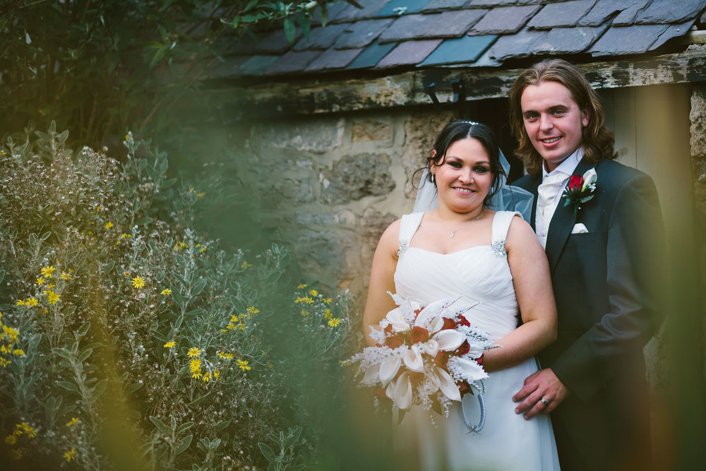 Bride and groom smile at the camera while surrounded by flowers