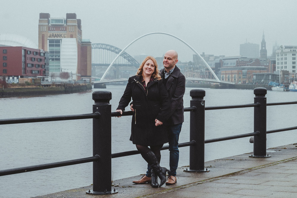 Engaged couple pose on foggy Quayside with Baltic and bridges in background