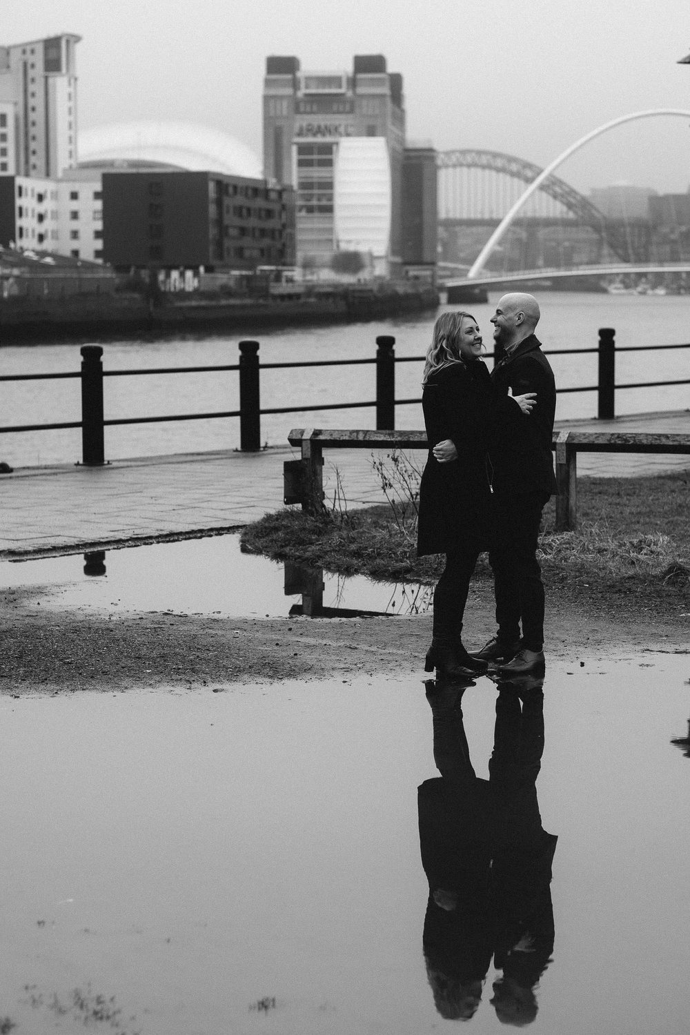 A black and white photo of a couple cuddling on Newcastle Quayside while reflected in a big puddle