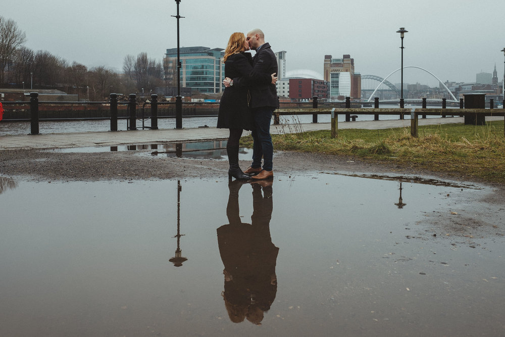 A couple kissing on Newcastle Quayside reflected in a big puddle