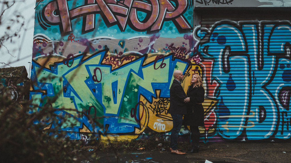 Couple hold hands in front of graffiti covered walls