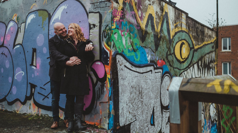 Couple cuddle on street corner covered in graffiti