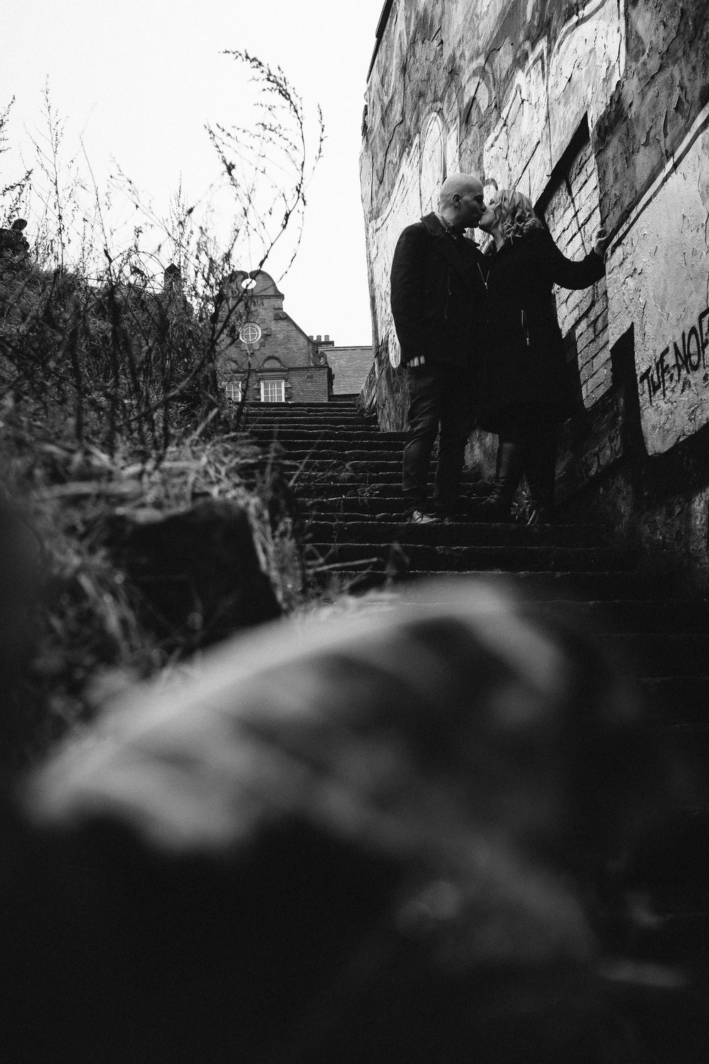 A black and white photo of a couple kissing on steps