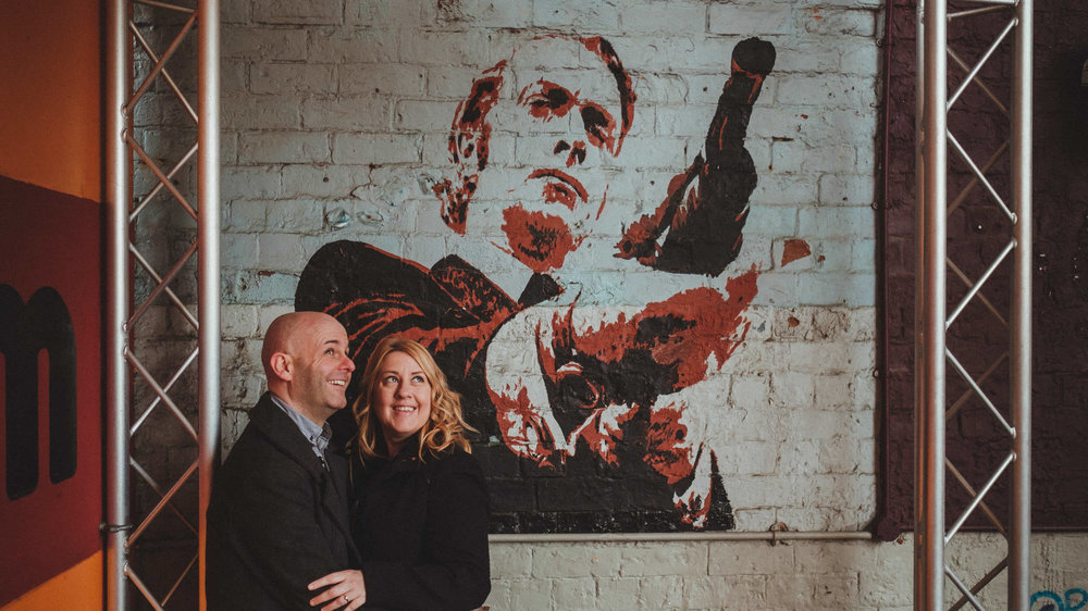Couple smiling in front of a wall with Michael Caine graffiti