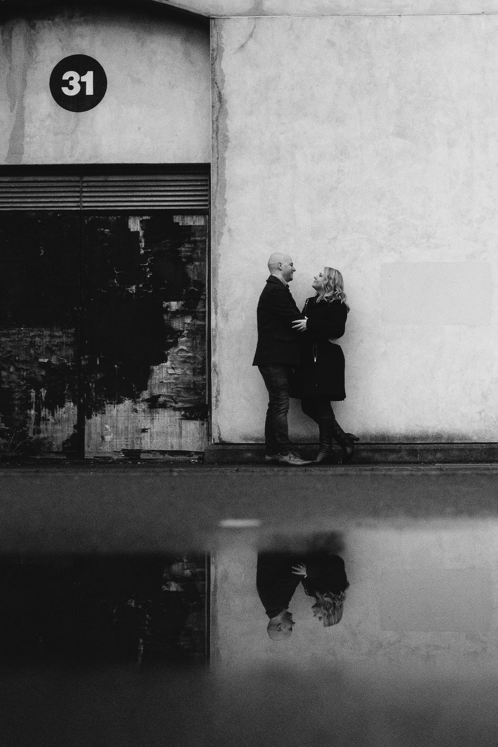 A black and white photo of a couple cuddling near a doorway with the paint peeling