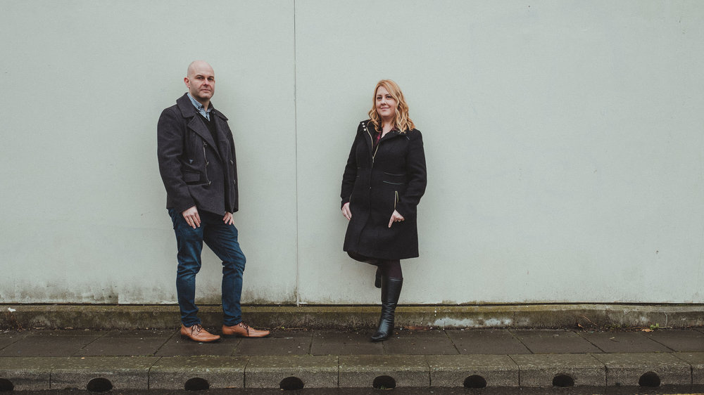 A couple lean against a wall on Newcastle Quayside