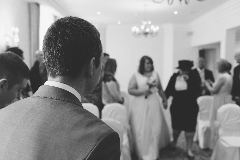 A black and white photo of the groom watching the entrance of his bride