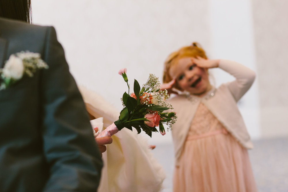 A flower girl pulls funny face during the wedding ceremony