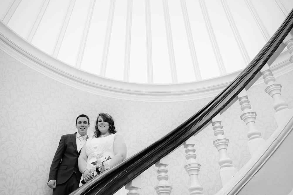 A black and white photo of the bride and groom posing on the staircase in the Grand Hotel