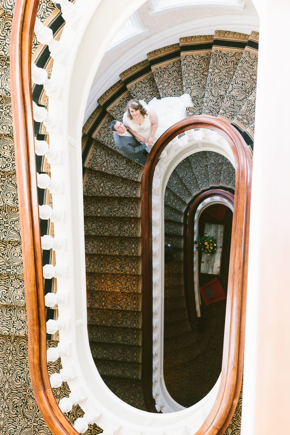 A photo looking down at the bride and groom on the staircase of the Grand Hotel