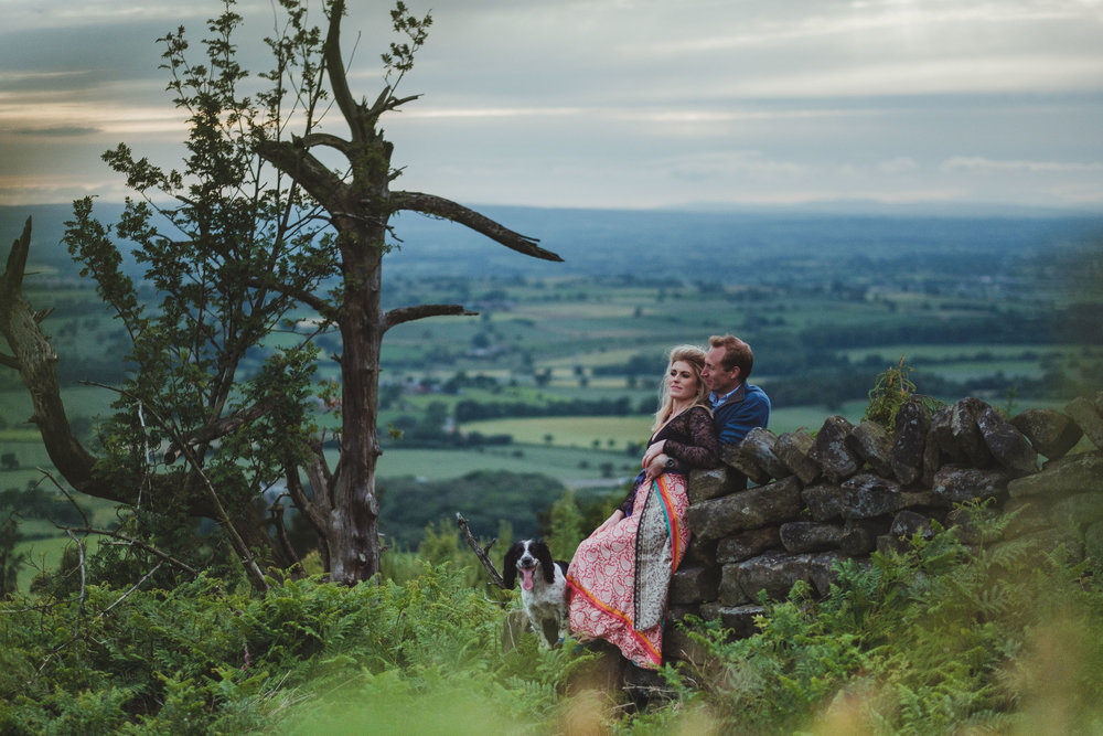 A couple sit on a drystone wall with a distinctive tree and the countryside behind them