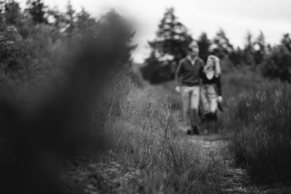A black and white photo of a couple walking arm in arm down a path