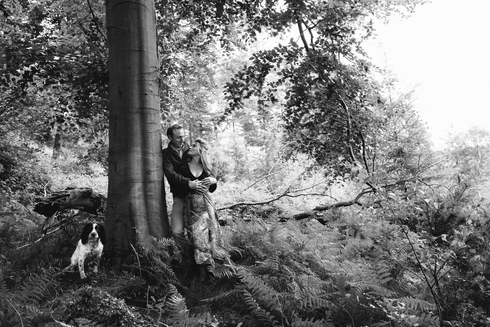 A black and white photo of a couple holding each other under a tree wile their dog watches on