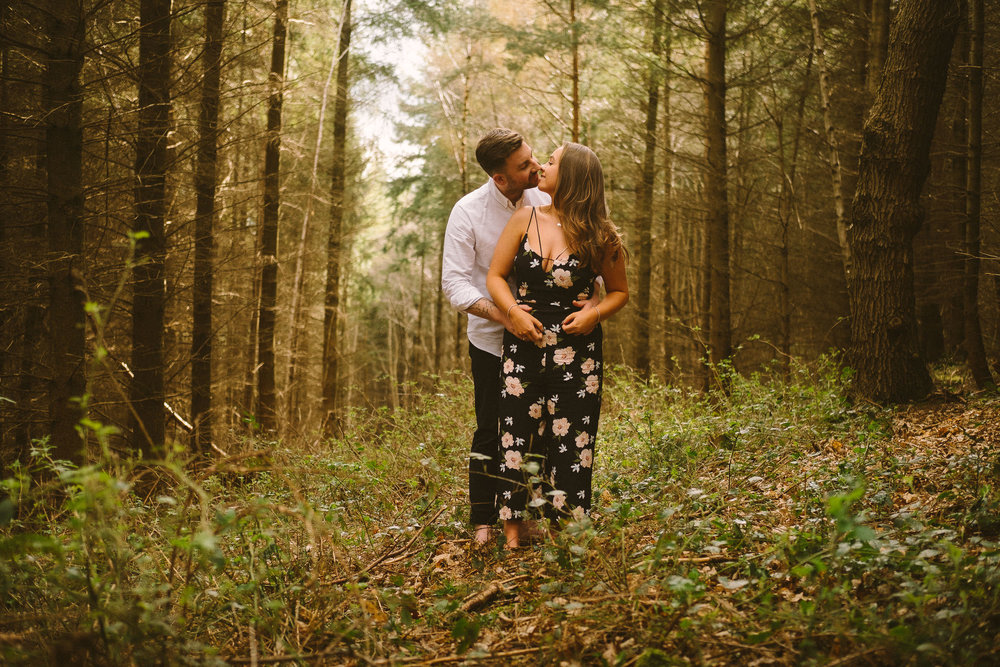 An engaged couple kiss while standing in wild woodland