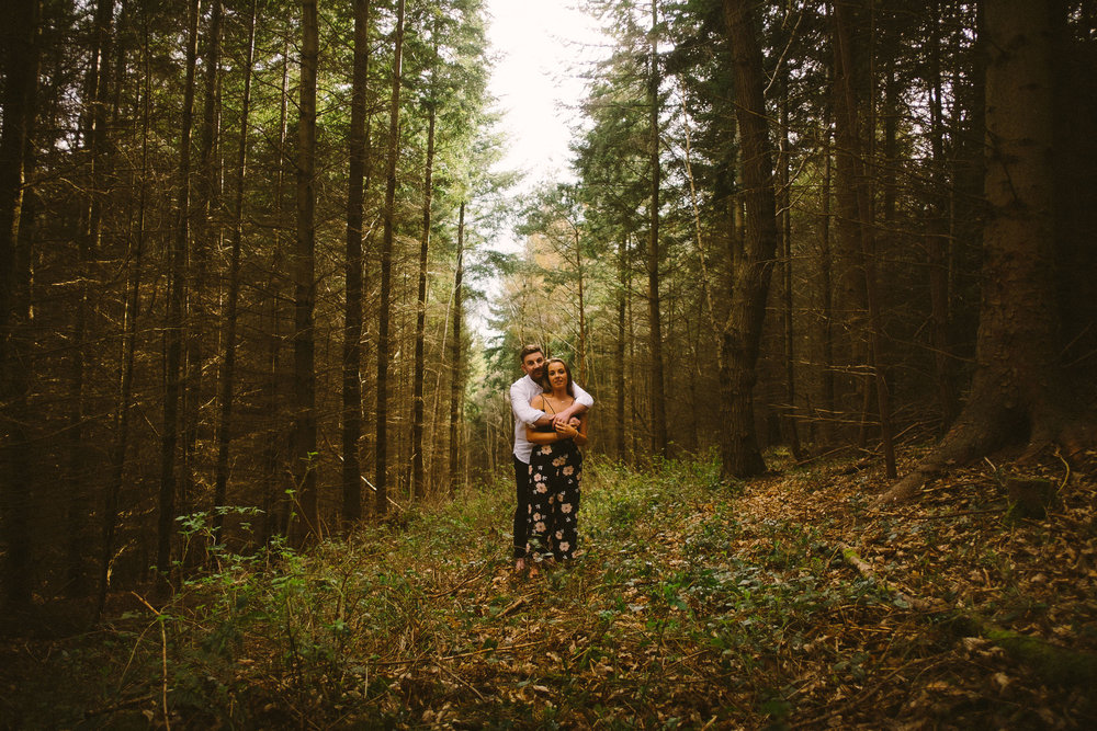A couple cuddle on a preceding shoot in Chopwell woods