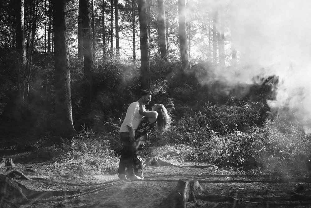 A black and white photo of a couple embracing passionately in the woods while smoke blows around them
