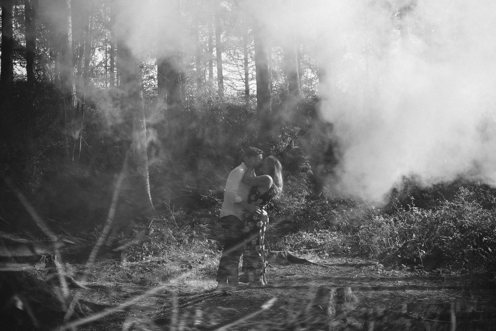 A black and white photo of a couple kissing while smoke fills the woodland around them