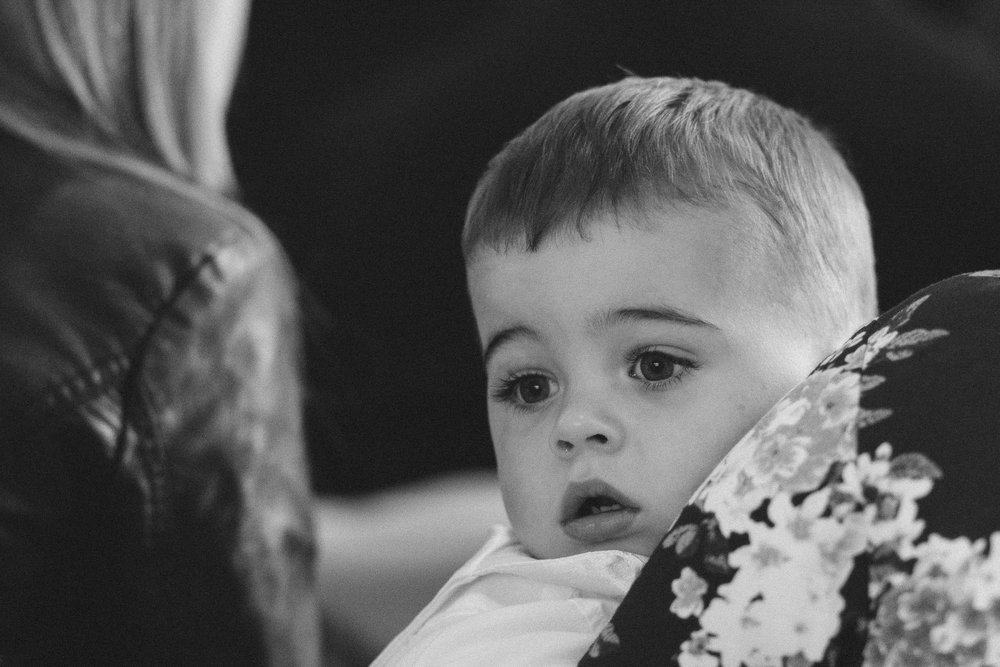 A black and white photo of a young boy waiting for the wedding ceremony to start