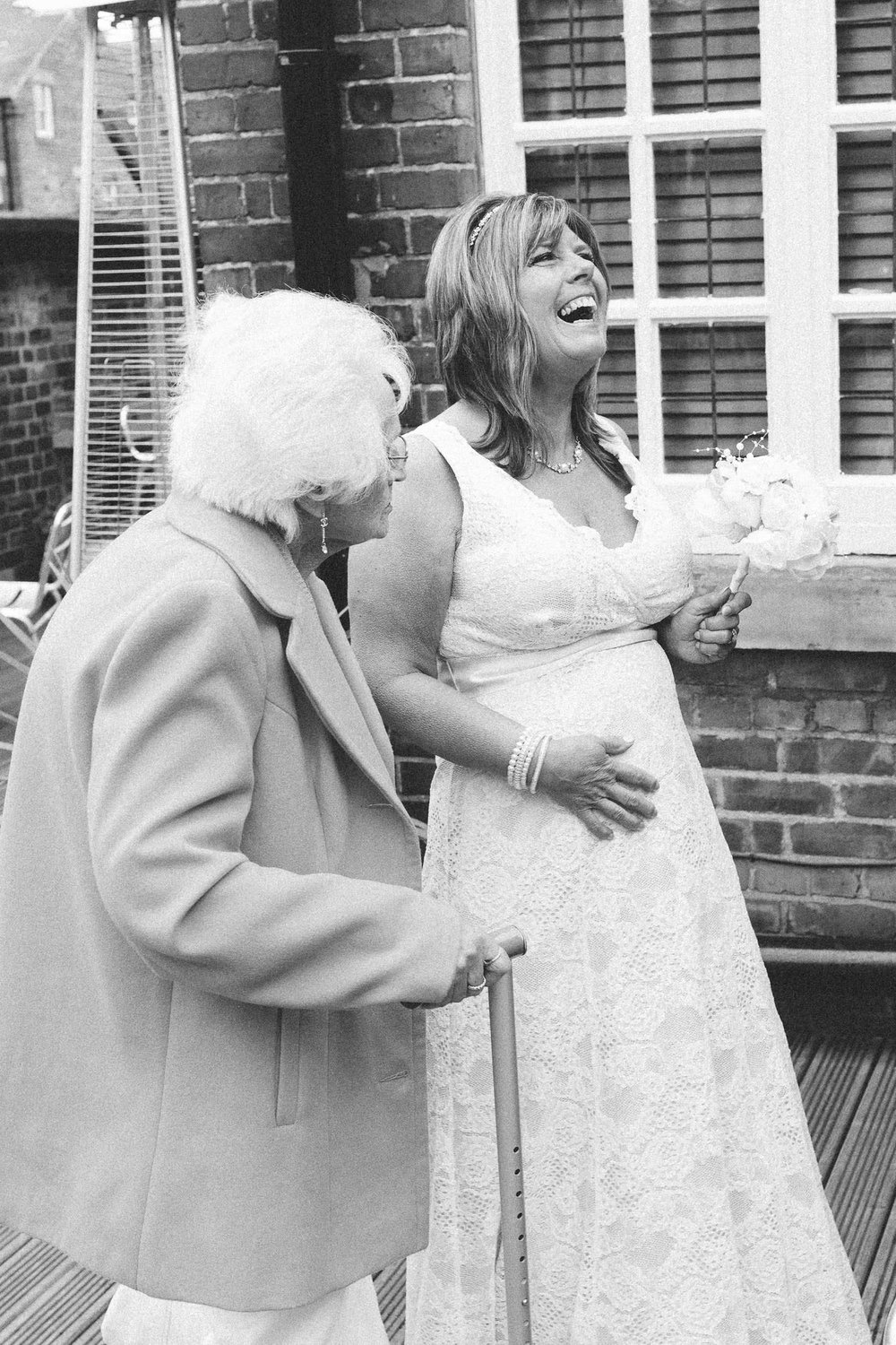 A black and white photo of the bride laughing while talking to an elderly relative