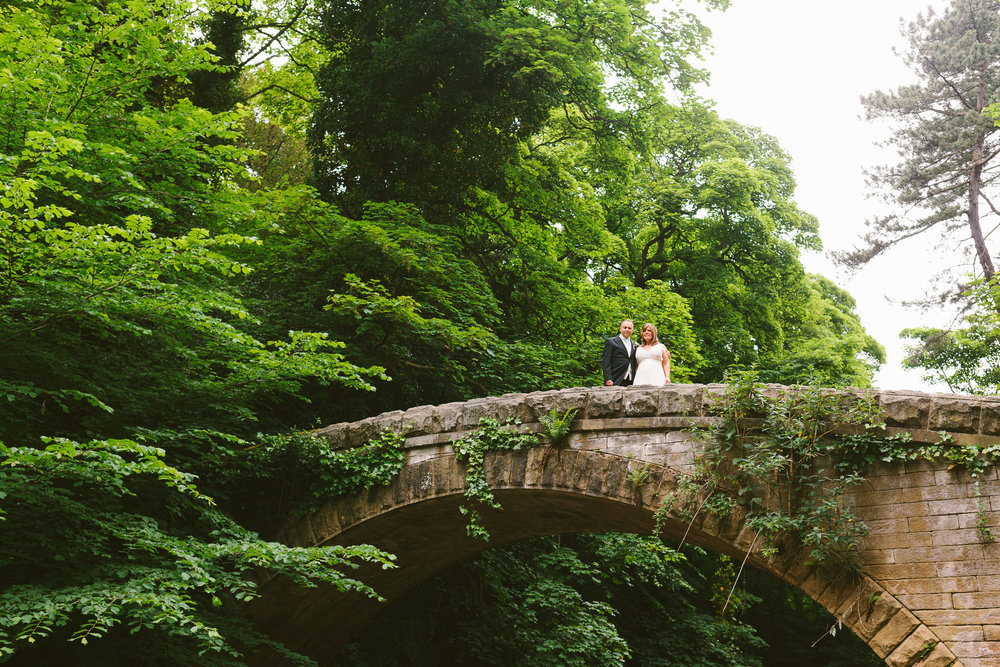 bride and groom stand on a stone bridge with tall trees behind
