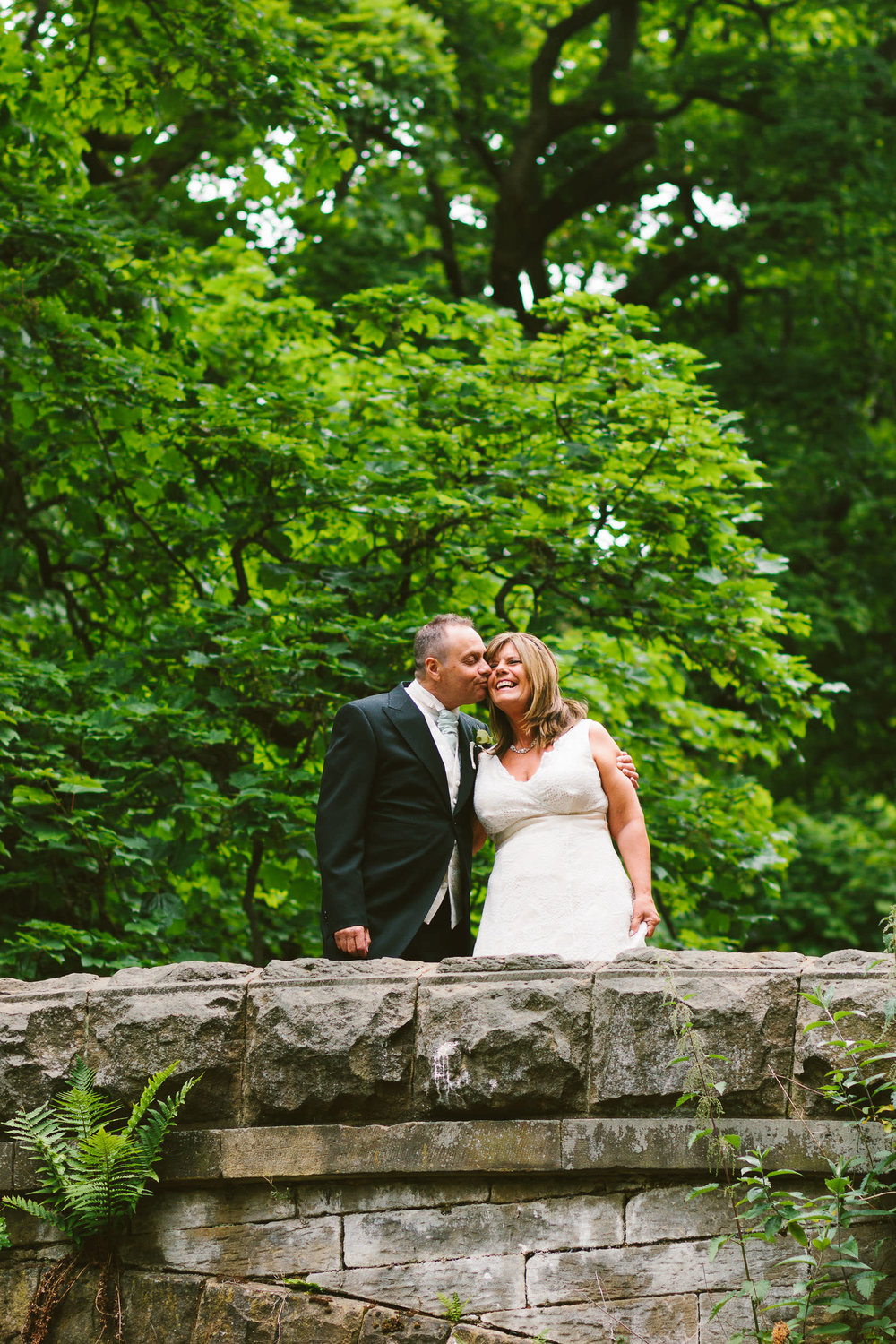 Bride and groom kiss and laugh while standing behind stone wall with trees behind