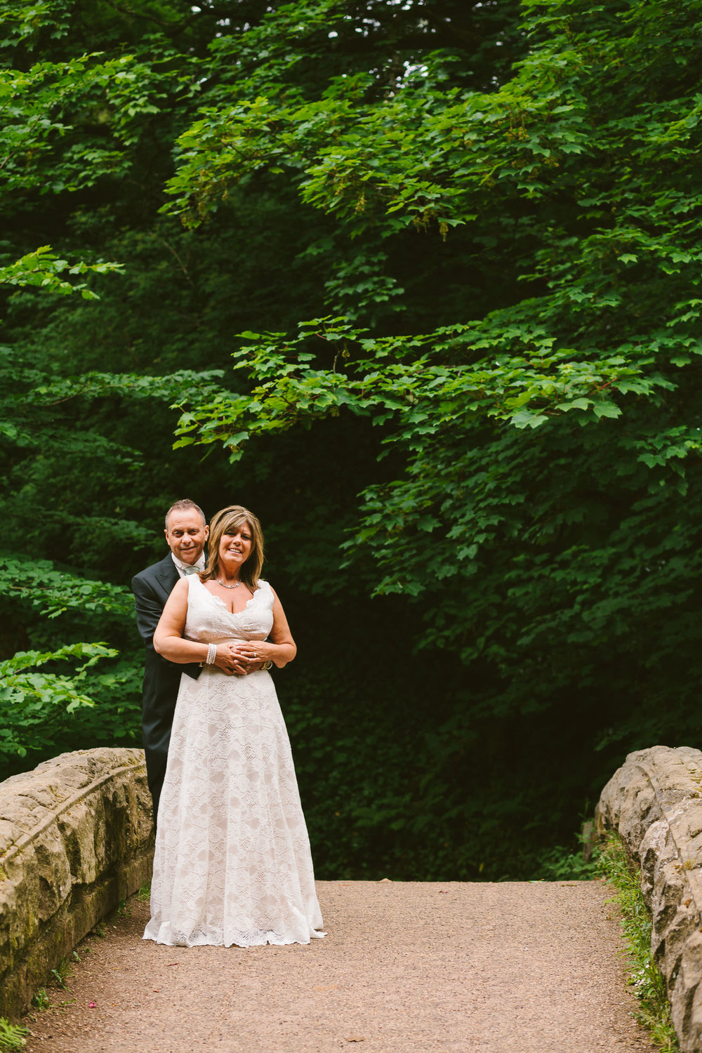 Bride and groom cuddle on bridge with forest in the background