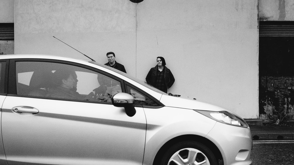 A black and white photo of a couple leaning against a wall while a car drive past