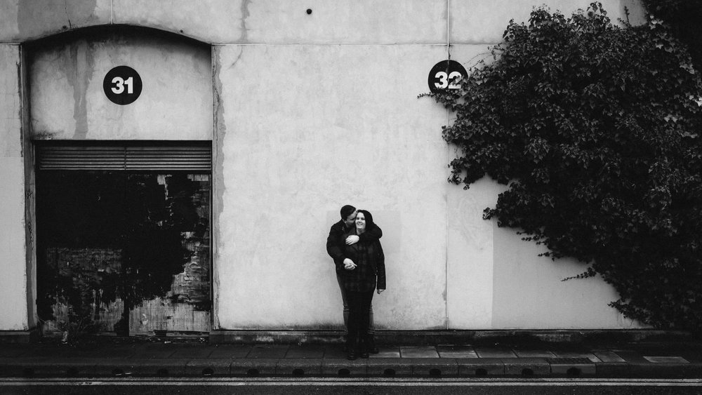 A black and white photo of an engaged couple cuddling on Newcastle Quayside
