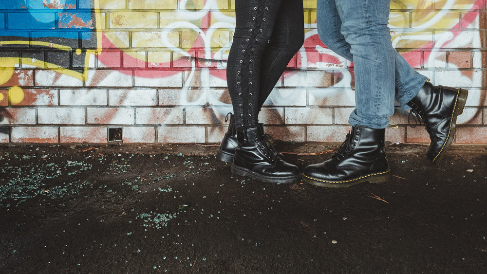 A close up of a couple wearing Doc Martin boots standing in front of a graffiti covered wall with broken glass on the floor