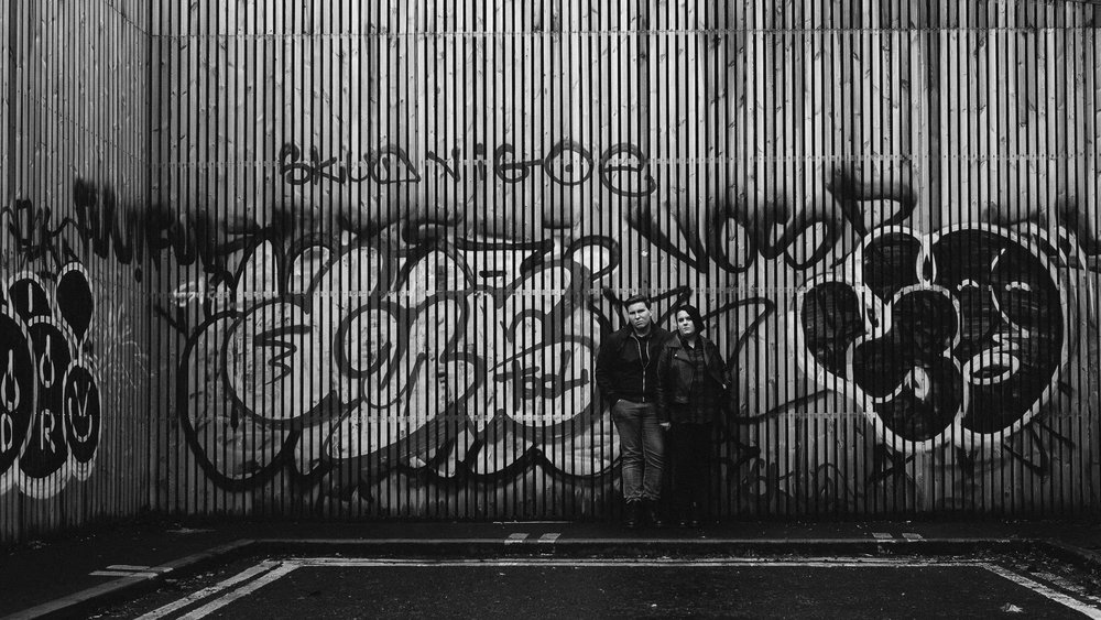 A moody black and white photo of a couple leaning against a wooden wall covered in graffiti