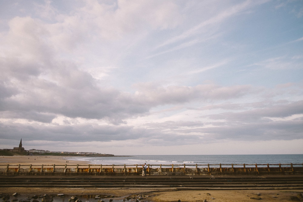 Engaged couple stand in ruined outdoor swimming pool with Tynemouth beach in the background