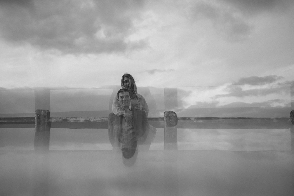 Black and white photo of couple looking at camera with reflections in prism