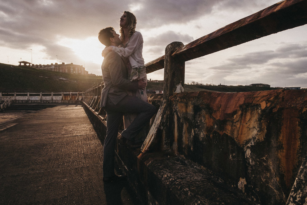 Dramatic photo of couple embracing near rusty fence with strong sunlight from behind