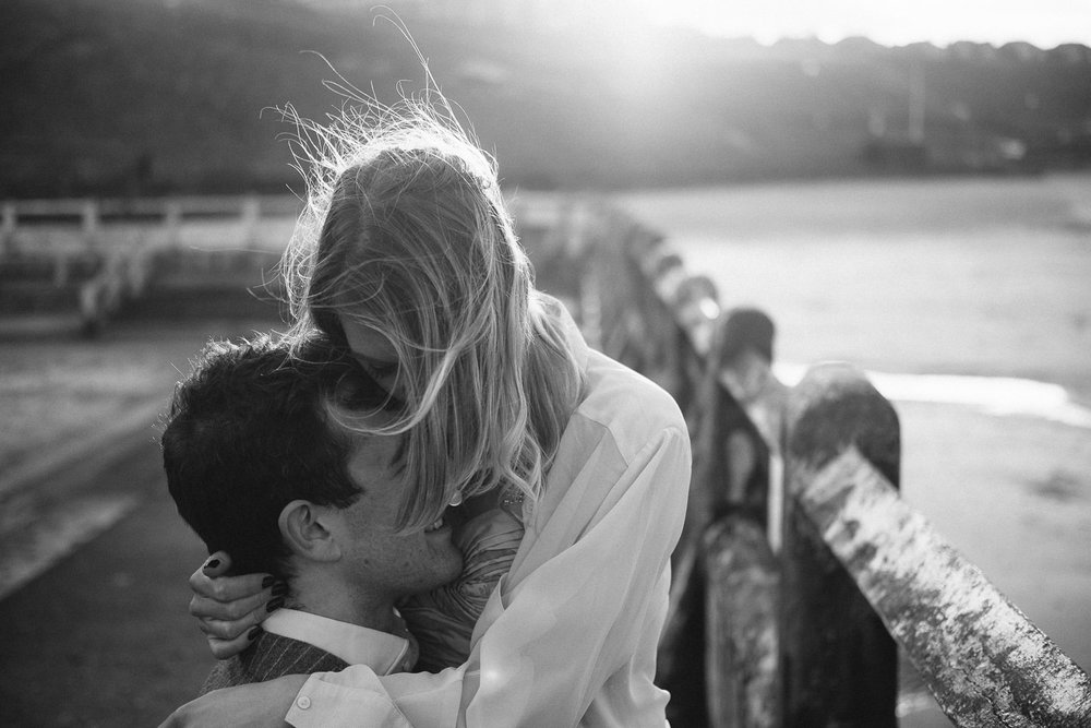 Black and white photo of engaged couple cuddling passionately backlit by the sun