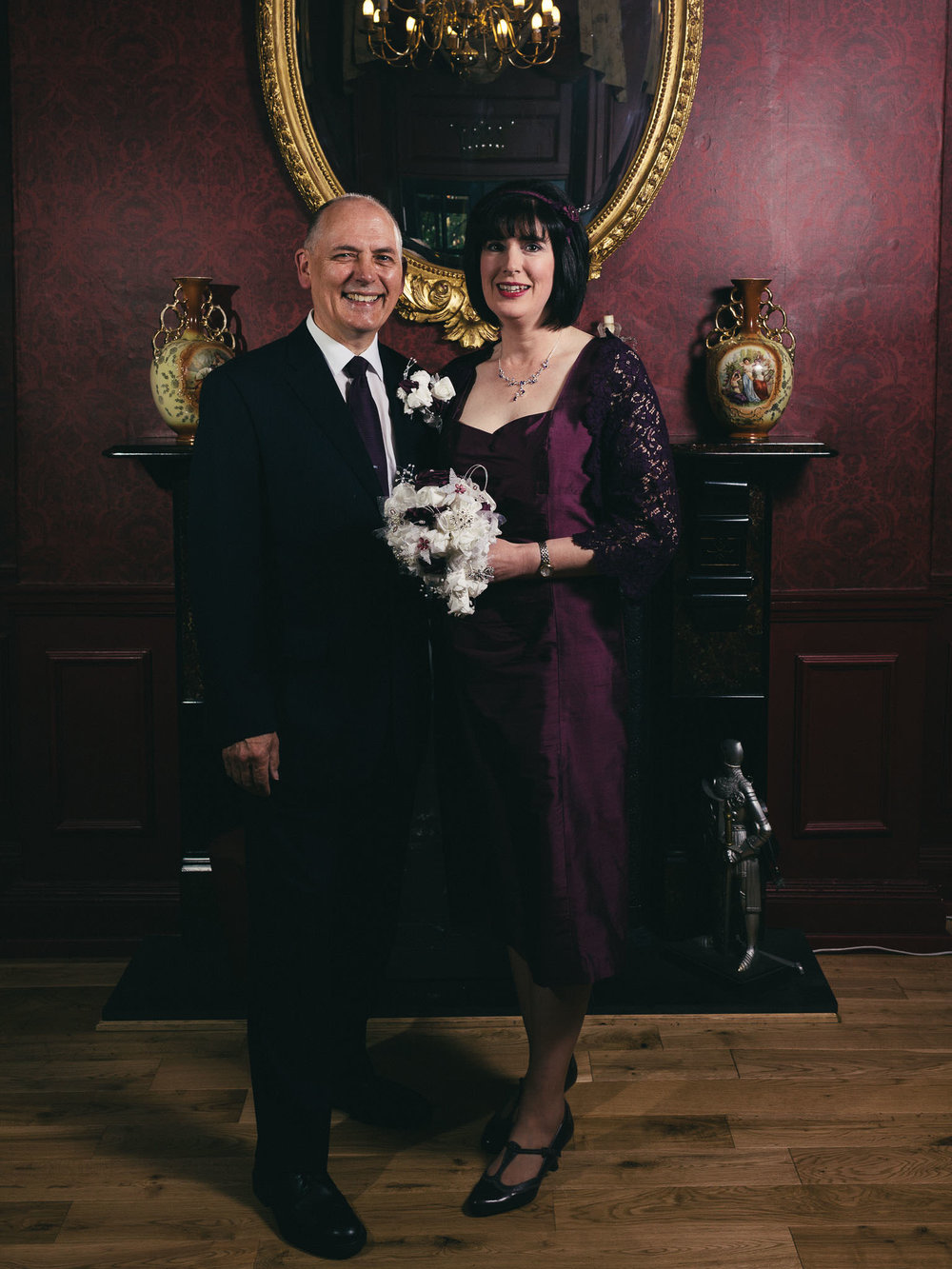 Bride and groom in front of an opulent fireplace before their wedding