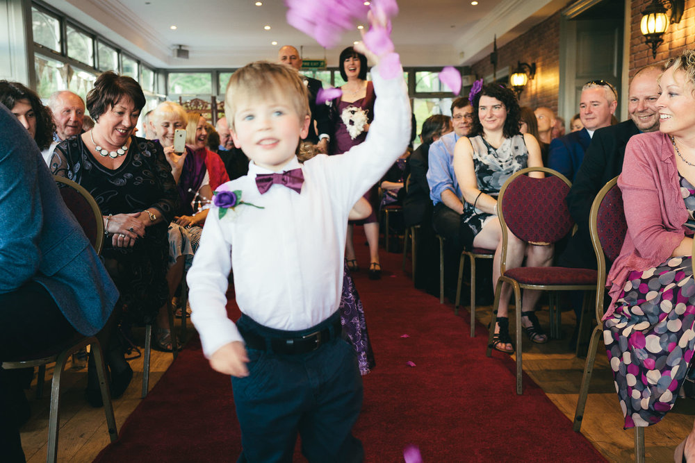 Page boy throws flower petals as bride and groom arrive at ceremony