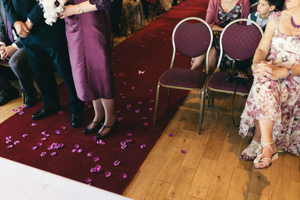 Flower petals scattered at the feet of the bride and groom during wedding ceremony