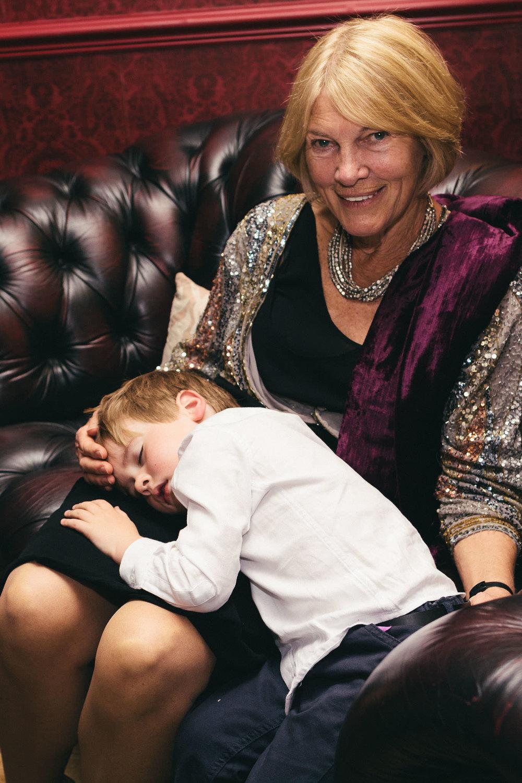 Boy lies asleep in grandma's arms