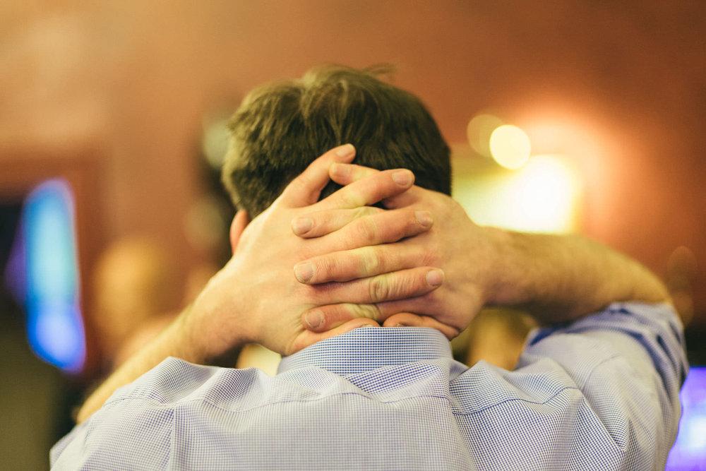 Guest crosses hands behind head at wedding reception