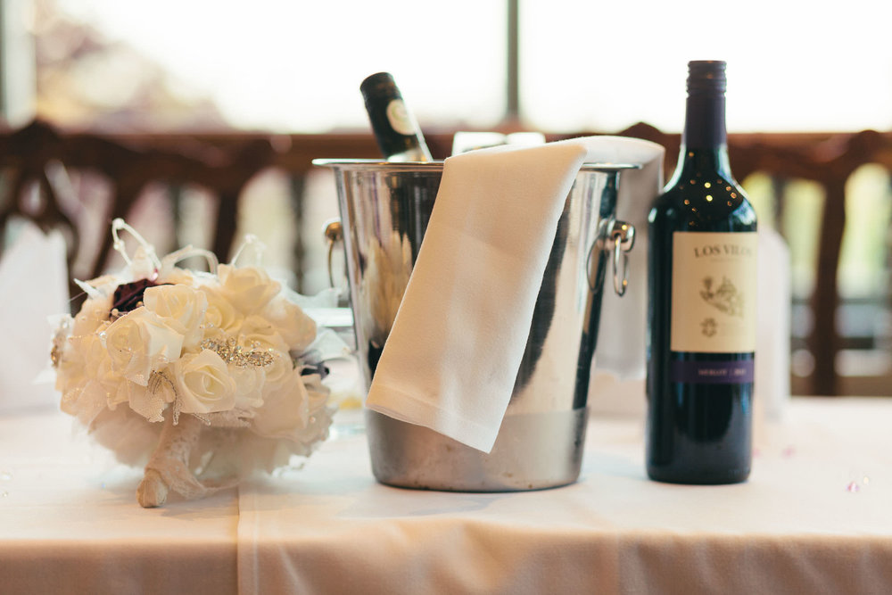 Close up of bride's flowers and wine bucket