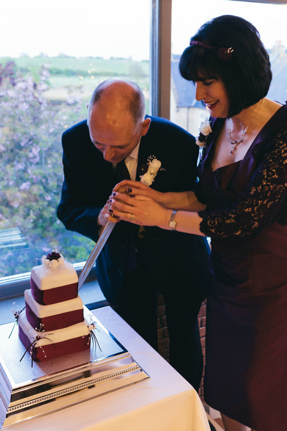 Bride and groom cut cake with sword