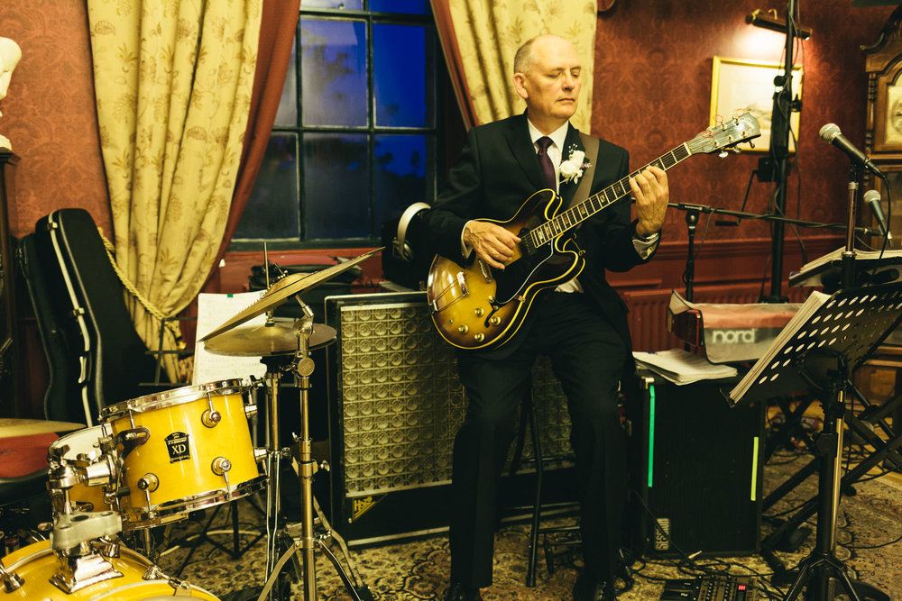 Groom plays guitar at wedding