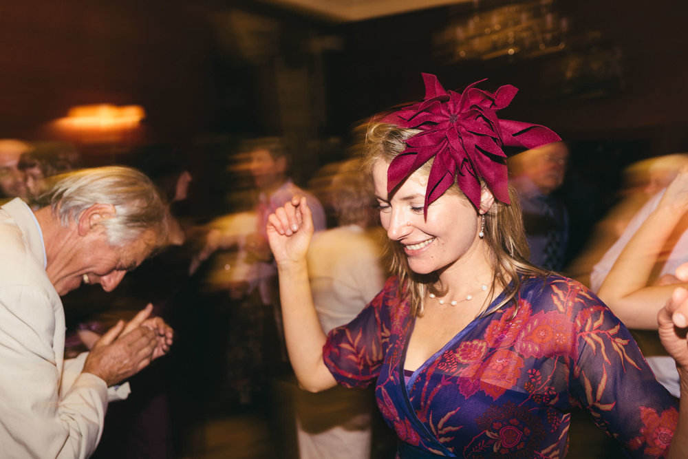 Wedding guest dressed in colourful outfit dancing