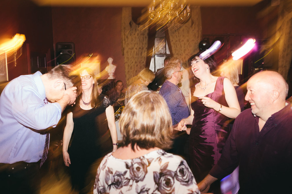 Bride laughs as she dances with wedding guests