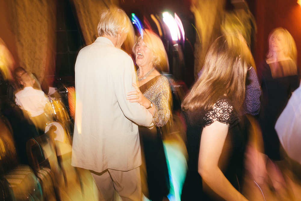 Older wedding guests dance and laugh