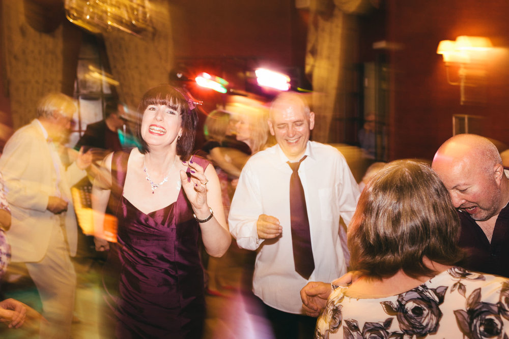 Bride and groom laugh and dance at the end of their wedding night