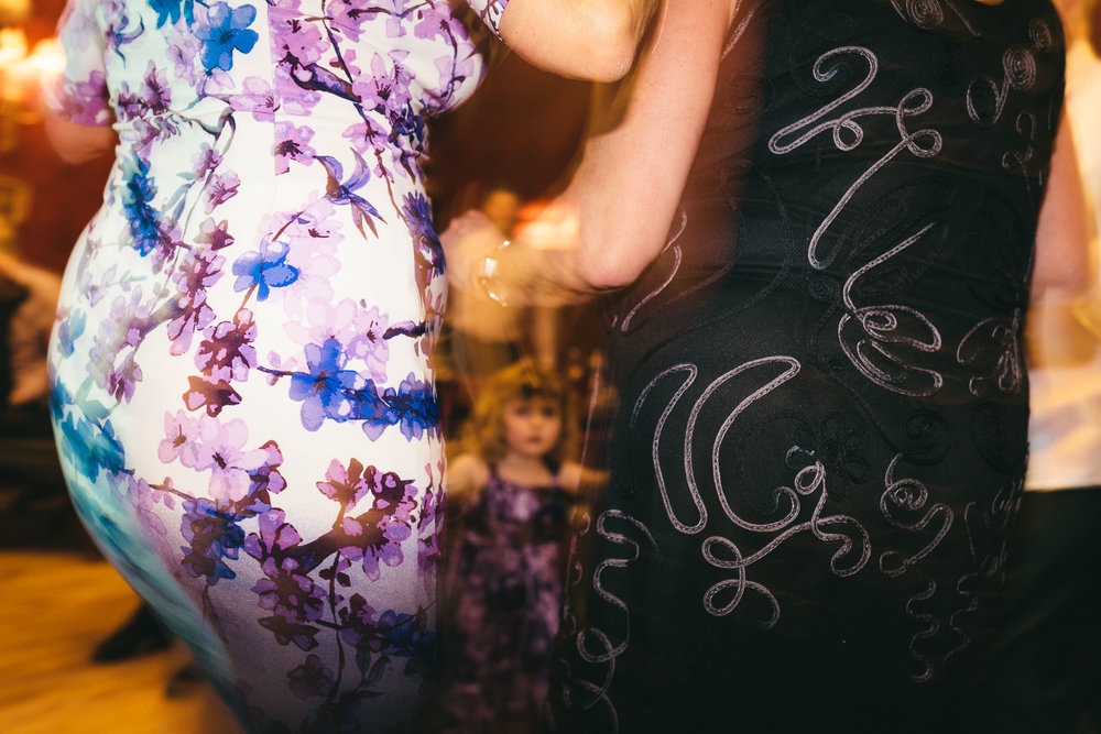 Small child glimpsed through dancing bodies at wedding