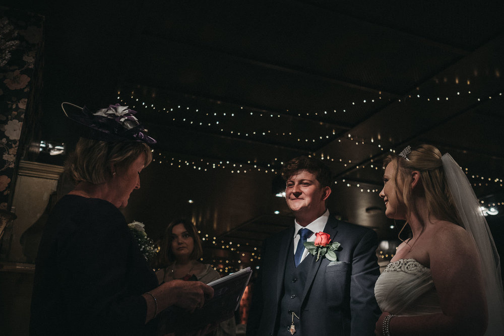 A dark room with harsh pools of light can feel romantic but makes a wedding photographer's job very tough!