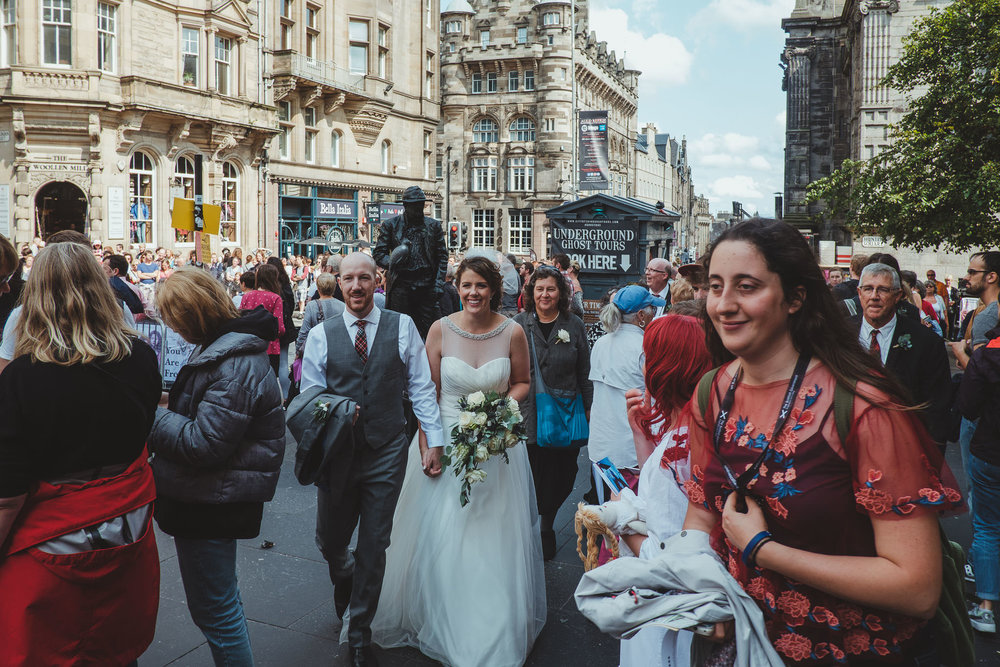 Angela and Andy pushing through the Fringe crowds during their Edinburgh elopement